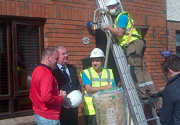Minister Rabbitte speaking to a local resident, along with Bayview Insulation Operatives Dominic McCrink and John Norris.